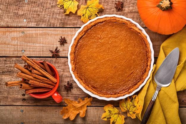 Torta di zucca. crostata con panna montata e cannella su fondo rustico. torta di zucca fatta in casa americana tradizionale per il ringraziamento o halloween pronto da mangiare. modello.