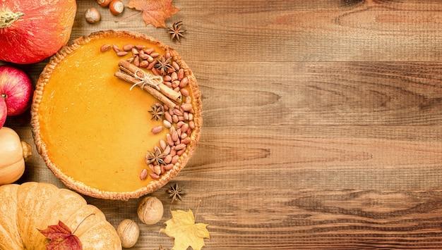 Zucca piepumpkinapplesnuts e foglie autunnali su un tavolo di legno per le vacanze di un tavolo per il ringraziamento