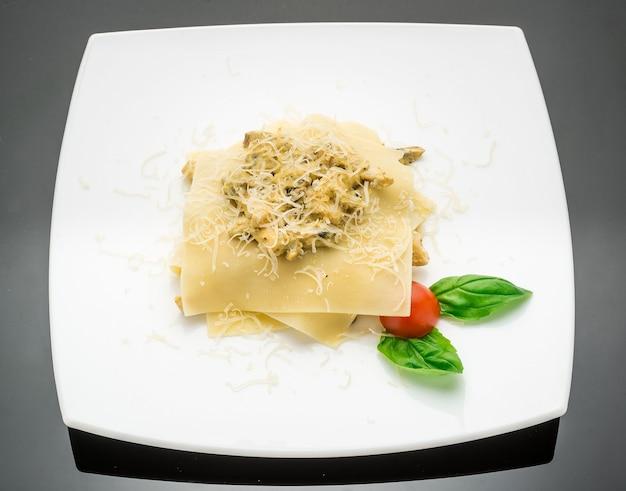 Lasagne di spinaci e ricotta di zucca su un fondo di legno bianco. il viraggio. messa a fuoco selettiva