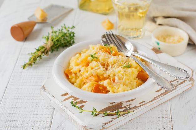 Risotto alla zucca con timo, aglio, parmigiano e vino bianco su fondo in legno chiaro stile rustico