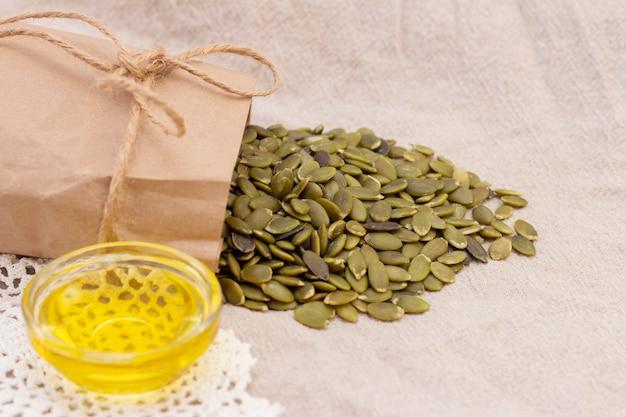 Semi di zucca in un sacchetto di carta, olio di semi di zucca su lino naturale. vitamine di semi di zucca del gruppo b e magnesio.