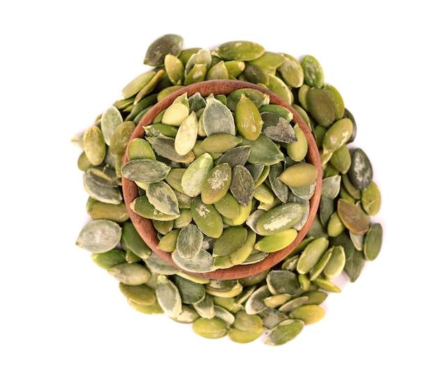 Semi di zucca in una ciotola di legno, isolati su sfondo bianco. semi di pepita verde. vista dall'alto.