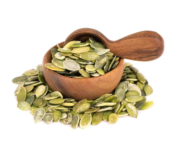 Semi di zucca in ciotola di legno e cucchiaio, isolati su sfondo bianco. semi di pepita verde.