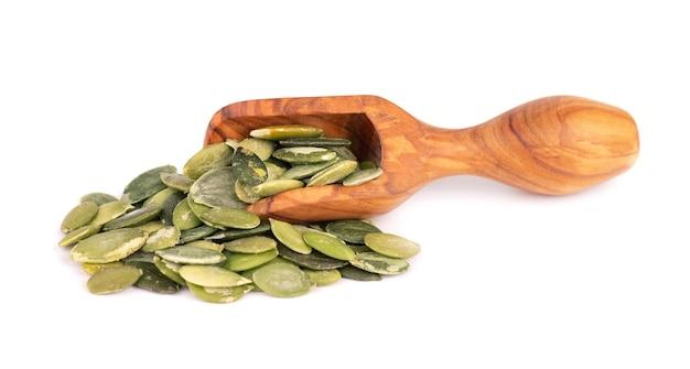 Semi di zucca in cucchiaio di legno, isolato su sfondo bianco. semi di pepita verde.