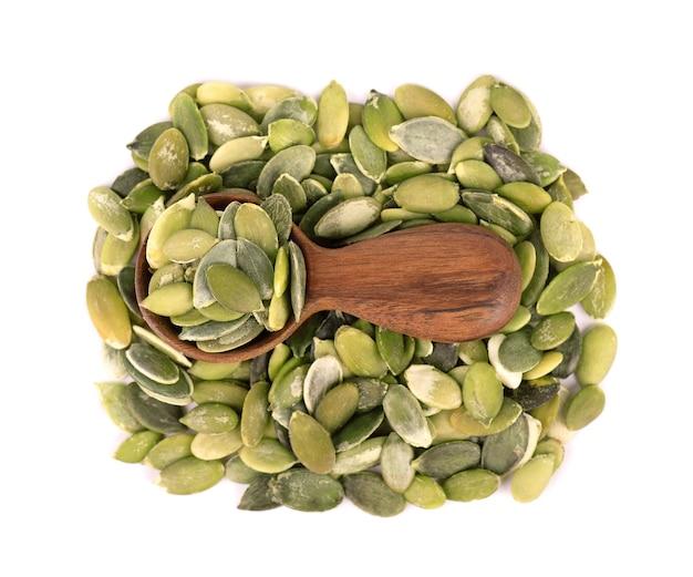 Semi di zucca in cucchiaio di legno, isolato su sfondo bianco. semi di pepita verde. vista dall'alto.