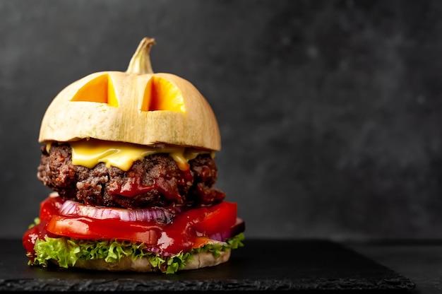 Hamburger a forma di zucca per la festa di halloween sul muro di pietra