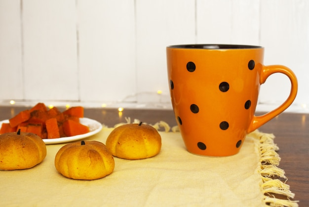 Pasticcini a forma di zucca sul tavolo accanto alla tazza