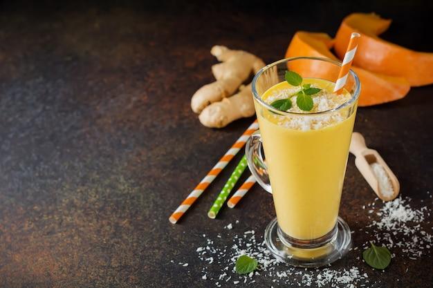 Frullati di zucca con zenzero e scaglie di cocco e menta in un bicchiere su una pietra scura o uno sfondo di cemento bevanda sana e deliziosa per la colazione