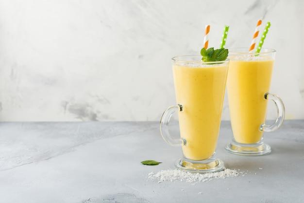 Frullati di zucca con zenzero e scaglie di cocco e menta in un bicchiere su pietra chiara o sfondo di cemento bevanda sana e deliziosa per la colazione