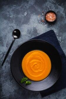 Zuppa di zucca in piatto di ceramica nera su fondo di legno scuro. cibo tradizionale autunnale. spazio di copia vista dall'alto.
