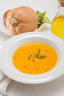 Zuppa di zucca e zucche organiche sulla tavola bianca. cibo autunnale stagionale - zuppa piccante di zucca e carote.