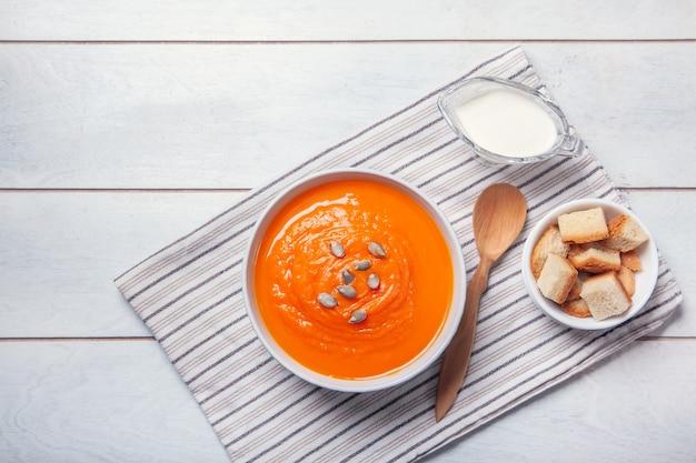 Purea di zuppa di zucca con pangrattato, panna e semi su un asciugamano, fondo di legno bianco.