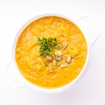 Zuppa di zucca in ciotola bianca su fondo bianco