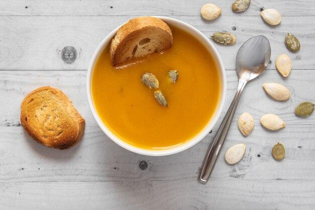 Zuppa di zucca con pane su fondo in legno chiaro con cucchiaio e semi