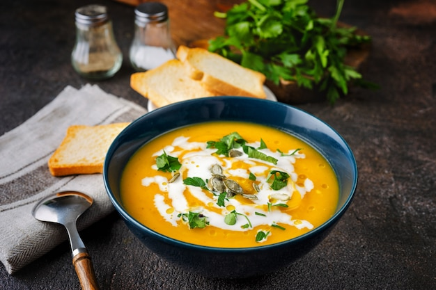 Zuppa di zucca con panna e prezzemolo sul tavolo rustico scuro