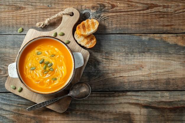 Zuppa di zucca con crostini di pane e panna.