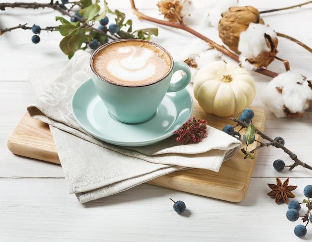 Latte alle spezie di zucca. tazza da caffè blu con schiuma cremosa, bastoncini di cannella, prugnole autunnali e piccole zucche gialle. bevande calde autunnali, caffetteria e concetto di bar