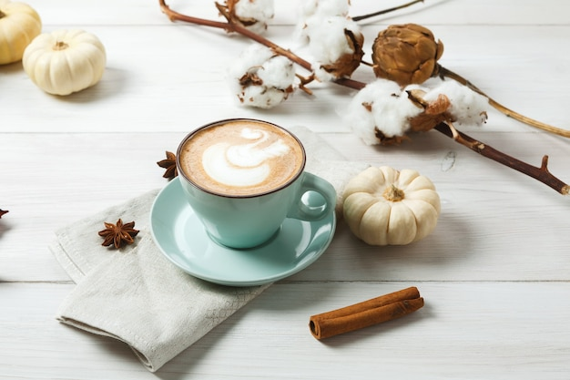 Latte alle spezie di zucca. tazza da caffè blu con schiuma cremosa, bastoncini di cannella e piccole zucche gialle. bevande calde autunnali, caffè e bar concetto