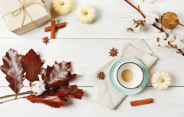 Tazza vuota del latte della spezia della zucca. tazza di caffè, bastoncini di cannella, foglie di quercia rossa e piccole zucche gialle. bevande calde autunnali