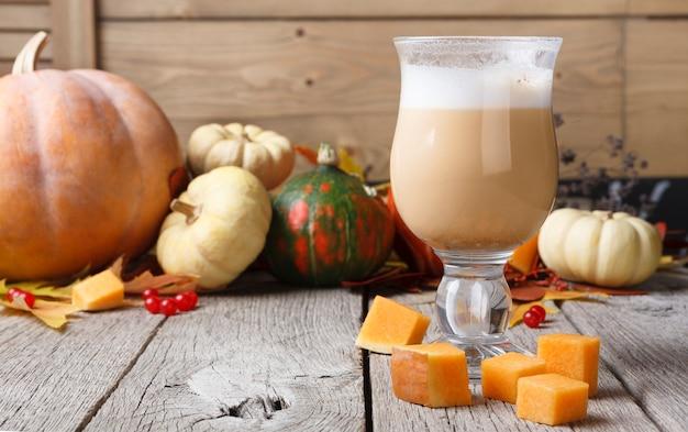 Latte alle spezie di zucca. tazza da caffè in vetro con schiuma cremosa, foglie secche autunnali, mele e piccoli cubetti di zucca gialla in legno rustico. bevande calde autunnali, concetto di offerta stagionale