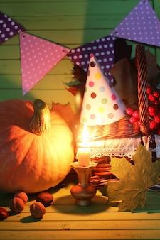 Cappello con candela natalizia zucca sul tavolo
