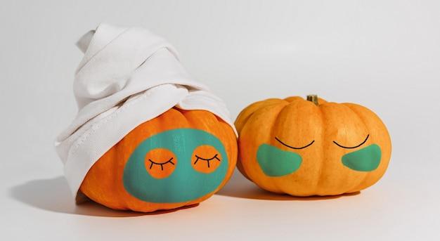 Zucca con maschera facciale e asciugamano isolato su sfondo bianco. spazio per il testo mockup spa e il concetto di halloween