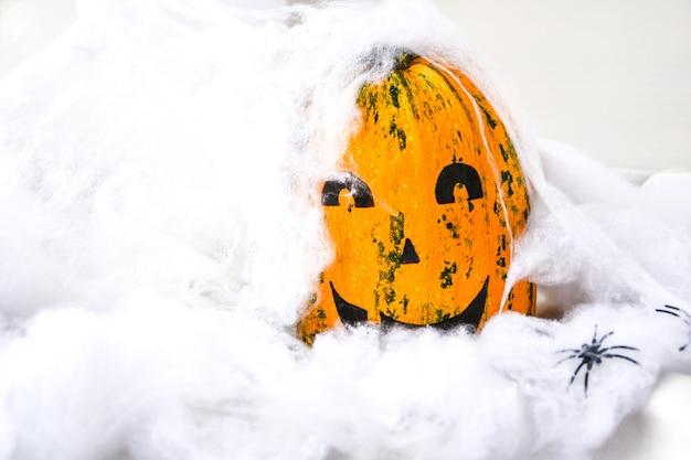 Zucca con la faccia dipinta su uno sfondo colorato per halloween. ragnatela. decorazioni per le feste. carta, copia spazio