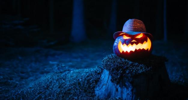 Zucca con un terrificante viso scolpito per halloween con retroilluminazione sullo sfondo di un glo...