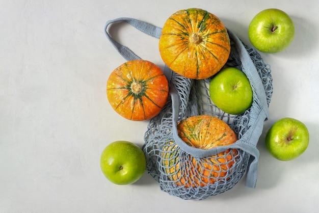 Zucche e mele in un sacchetto di corda ecologico.