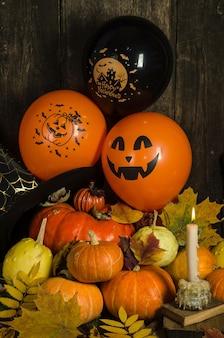 Zucche e palloncini con candela e foglie d'autunno