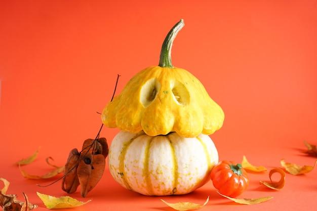 Zucche, foglie secche su sfondo arancione. concetto di halloween. composizione autunnale.