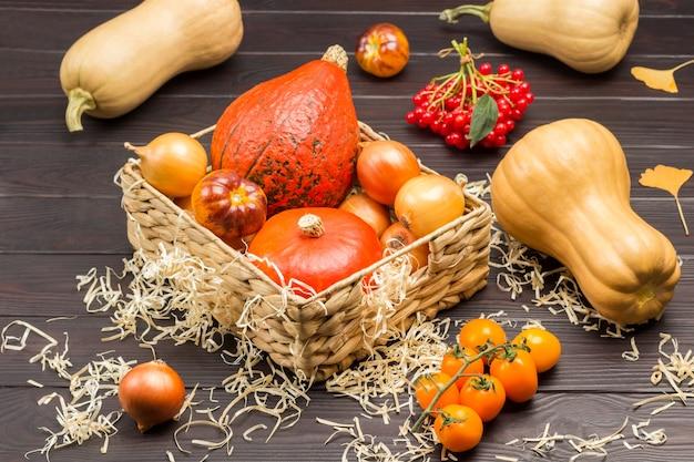 Zucche e cipolle in cesto di vimini. ramo di pomodori gialli, rametto di viburno e zucca sul tavolo. fondo in legno.