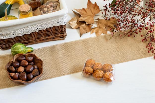 Zucche spezie e nocciole confezionate in cesto regalo artigianale castagne e panelles de piones sul bianco tavolo rustico