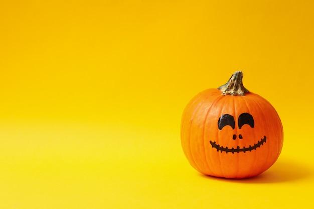 Zucche con la faccia sorridente sul giallo
