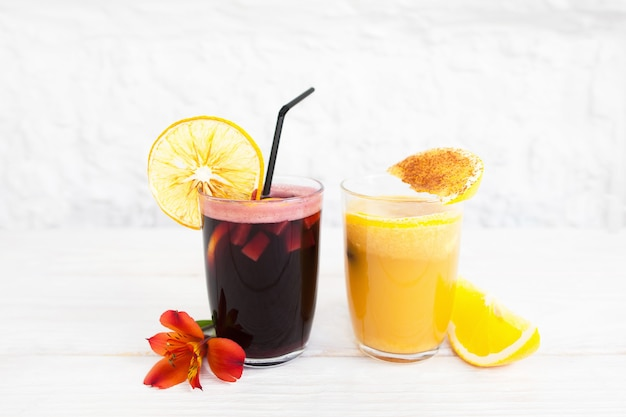 Punch e bicchieri di succo d'arancia su bianco