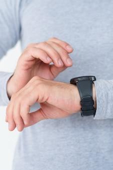 Puntualità, autodisciplina e gestione del tempo. uomo che guarda l'orologio sulla sua mano controllando se è nei tempi previsti.