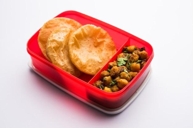 Punjabi chole o choley masala con puri o poveri in scatola per il pranzo o tiffin, fuoco selettivo
