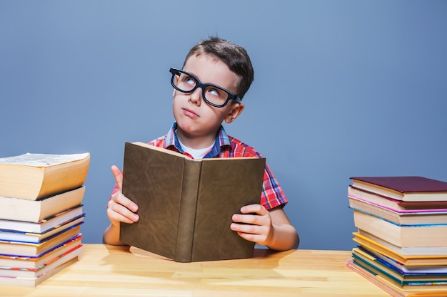 Allievo con gli occhiali che ottiene la conoscenza da un libro di testo