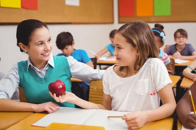 Allievo che offre una mela all'insegnante