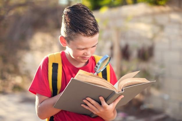 Allievo con libro e lente d'ingrandimento all'aperto. di nuovo a scuola. bambini e concetto di educazione