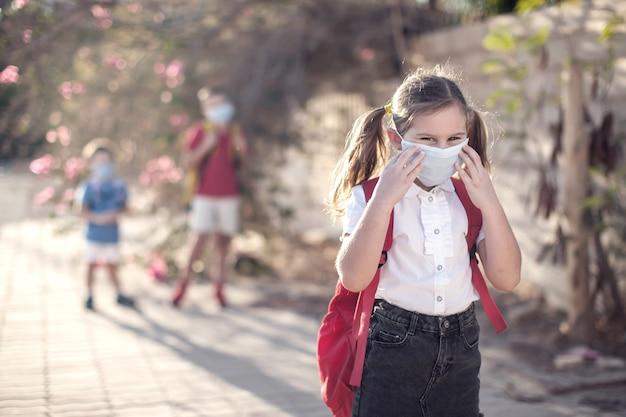 Allievo con mascherina medica sul viso e zaini all'aperto. istruzione durante il periodo del coronavirus. bambini e assistenza sanitaria. di nuovo a scuola.