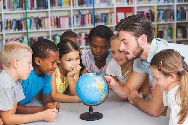 Alunni e insegnante guardando il globo in biblioteca