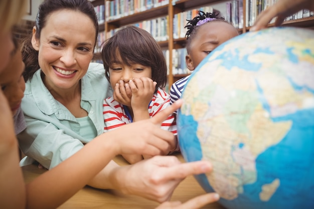 Allievi ed insegnante che esaminano globo in biblioteca