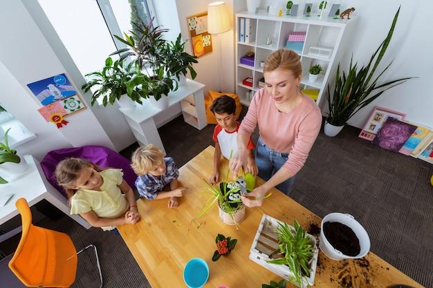 Alunni che guardano. vista dall'alto degli alunni che guardano l'insegnante dai capelli biondi usando le pinze per tagliare i bordi asciutti della pianta