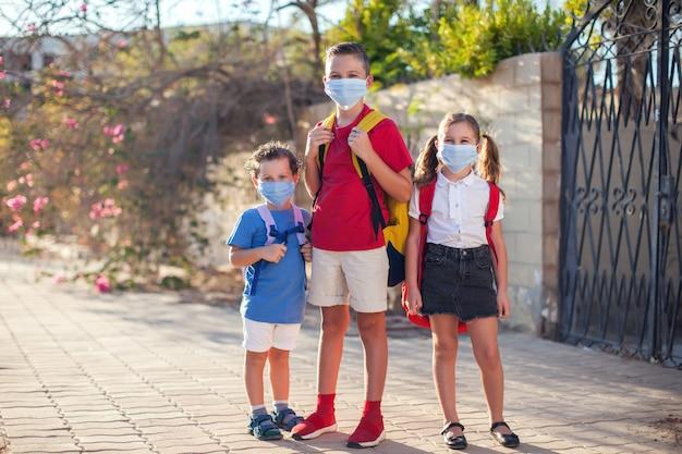 Alunni con maschere mediche sul viso e zaini all'aperto. istruzione durante il periodo del coronavirus. bambini e assistenza sanitaria. di nuovo a scuola.