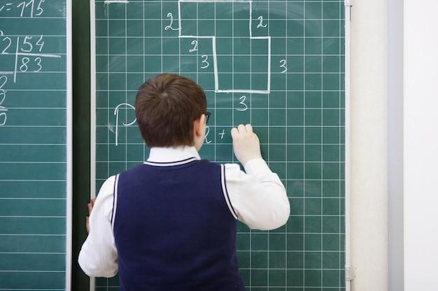 Gli alunni scrivono sul numero del gesso della lavagna, risolve i compiti matematici