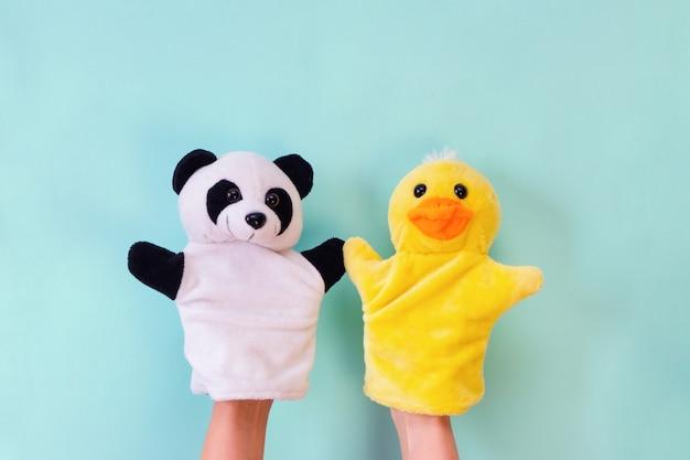 Giocattoli del teatro delle marionette su una mano su uno sfondo turchese. concetto di intrattenimento per bambini. anatra e panda