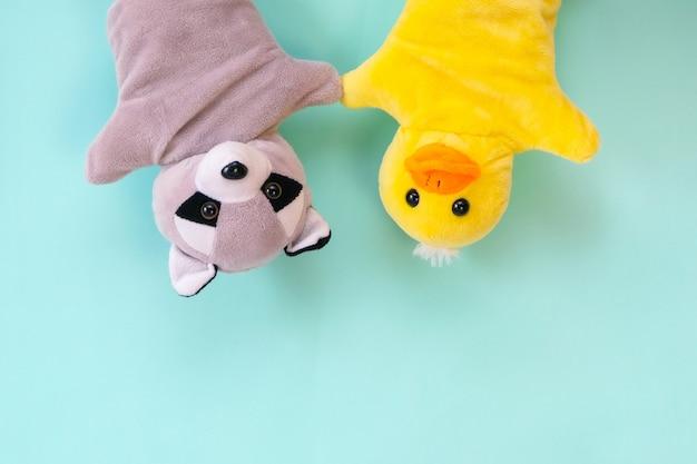 Giocattoli del teatro delle marionette su una mano su uno sfondo turchese. concetto di intrattenimento per bambini. procione e anatra
