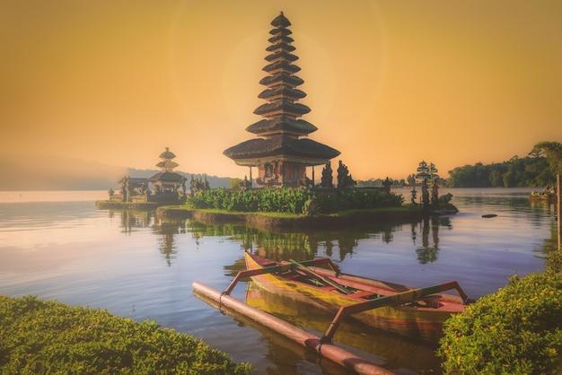 Pura ulun danu bratan, tempio indù con barca sul paesaggio del lago bratan all'alba a bali, indonesia.
