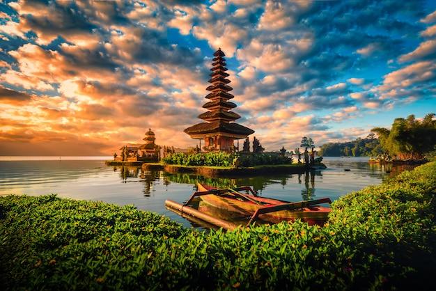 Pura ulun danu bratan, tempio indù con la barca sul paesaggio del lago bratan ad alba in bali, indonesia.